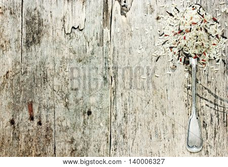 Mixed rice in vintage metal spoon on old wooden background top view empty space for text