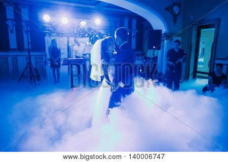 Wedding dance of newlywed bridal couple. The hall is covered with white fume and filled by blue lights.