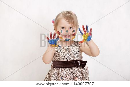 Little beautiful girl draws paints on the face and hands of paint