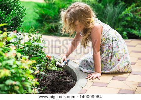 Little blonde girl planting flower in a garden.