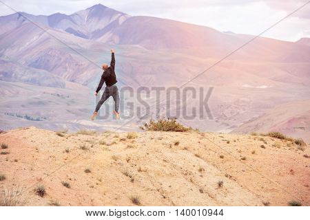 bald man jumping on top of a mountain of joy