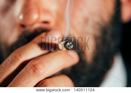 Close-up of a man smoking a joint