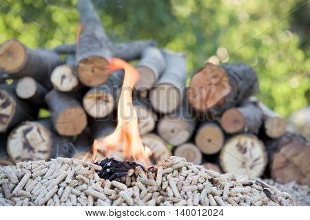 Fir Pellets in flames in front a pile of wood