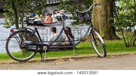 The tandem bicycle and back view of young couple relaxing near the water.