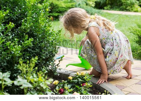 Cute little girl watering plants in the garden.
