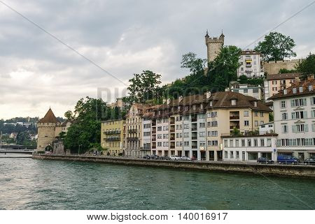 Luzerne, Switzerland - August 23, 2010: Tower of old city wall and houses on embankment of Reuss River in old town of Lucerne ( Luzerne )Luzerne Switzerland - August 23 2010: Tower of old city wall and houses on embankment of Reuss River in old town of Lu