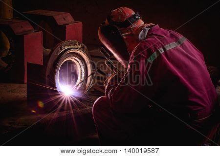 Welding steel structures and bright sparks with lens flare in construction industry.