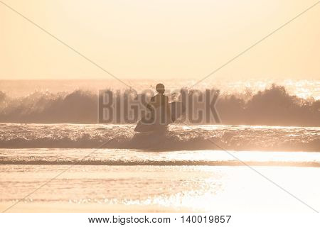Male surfers on sandy beach with the surfboard in sunset.