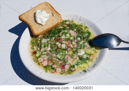 The traditional Russian cold soup okroshka sour cream sandwich and spoon