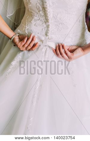 Closeup shot of elegant, bride in vintage white dress fixing her dressing at wedding preparations. Back view.