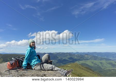 The girl in the campaign sitting on a rock in the mountains against the blue sky.