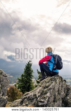 Woman hiking in autumn mountains and woods. Sitting on rock and relaxing recreation and healthy lifestyle outdoors in fall nature. Beauty blond looking at sunset inspirational landscape view.