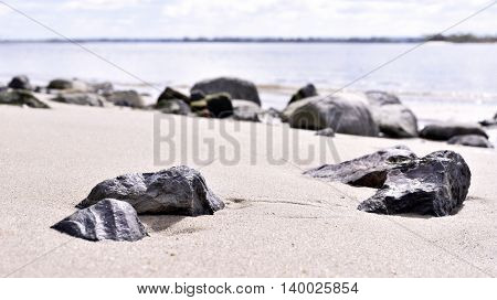 close-up and selective focus of rocks or stones at the beach. Elbstrand, Hamburg - Germany. River and horizon over land. Sunny day at the beach. Nature background with copy space.