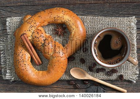 Soft pretzels with cup of hot coffee for breakfast on a rough fabric located on the table top view
