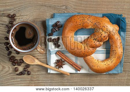 Sweet pretzels with cup of hot coffee for breakfast on napkin located on the table. View from above