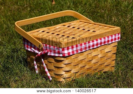 A picnic basket sits in the grass