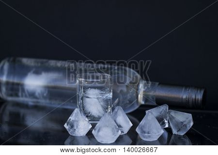 A bottle of vodka and a glass with ice alcoholic drink close-up on a black background