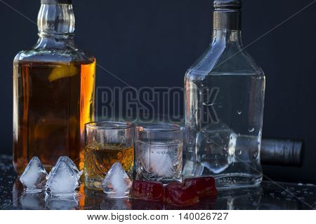 Vodka and whiskey in the bottle vodka and whiskey in glass with ice alcoholic drink