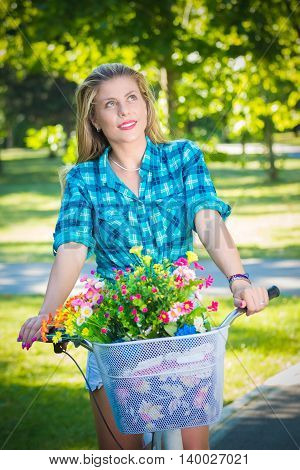 Elegant female on retro hipster bike with basket full of flowers in a park. Active people, vacation, and lifestyle concepts.