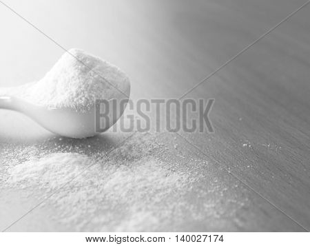 spoonful of baking soda on the wooden background
