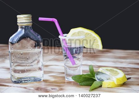 Vodka. Small bottle of vodka with a glass ice and lemon on the table. black background closeup