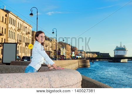 beautiful girl walks on the promenade at sunset