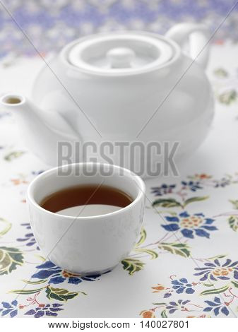 white tea pot and tea cup