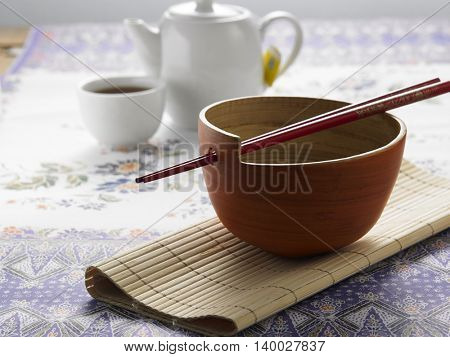 chopstick rest on the bowl with tea pot as background