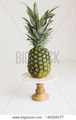 Pineapple on pedestal with white seamless background