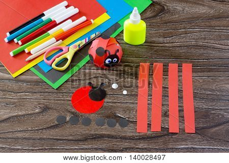 The Child Makes Crafts Out Of Paper Ladybug. Glue, Paper, Scissors On A Wooden Table. Children's Art