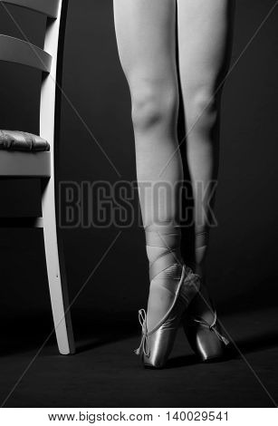 Black and white image of ballerina legs, chair brings more dynamic to the photo