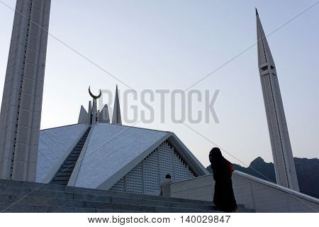 Muslim woman walking into the Faisal Mosque in Islamabad.