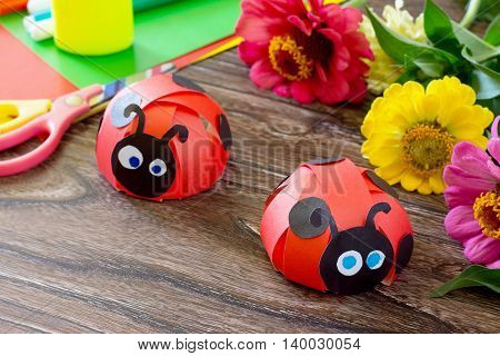 Colorful Paper For Children Handmade Odd Job Ladybug On A Wooden Table And The Flowers. School And K