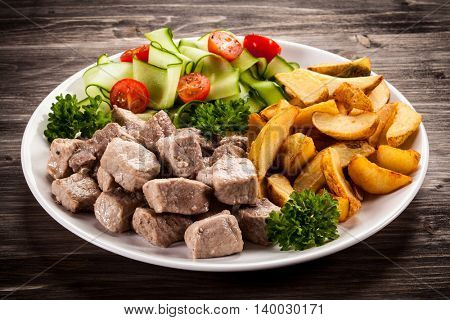 Grilled meat with baked potatoes and vegetables