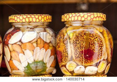 Homemade honey with dried fruits and nuts on the market.