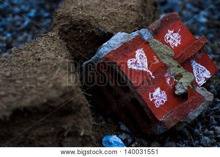 focused broken heart-painted brick on the ground