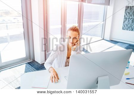 Attractive young woman sitting at desk and working on her computer