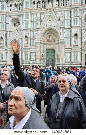 FLORENCE, ITALY - APRIL 27: Tourists on Piazza del Duomo in front of the cathedral of Florence - Dom Santa Maria del Fiore on April 27, 2013 in Florence. Cathedral is part of the UNESCO World Heritage