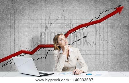 Thoughtful businesswoman sitting at table and graphs and diagrams at background