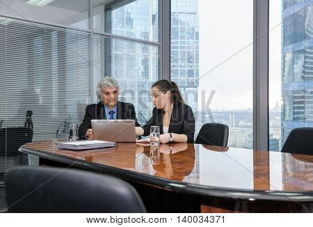 Mature businessman and young business woman discussing in a modern office