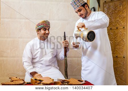 NIZWA, OMAN, MAY 27, 2016: two Omani men having traditional Omani coffee