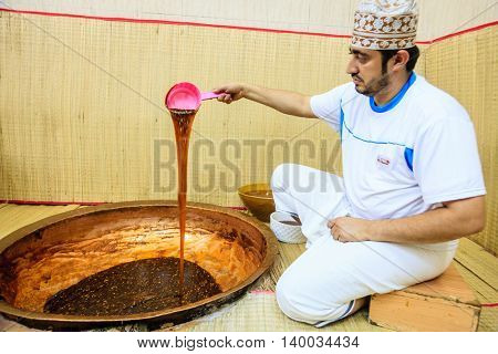 NIZWA, OMAN, MAY 27, 2016: factory  worker checks consistency of freshly made traditional Omani halwa