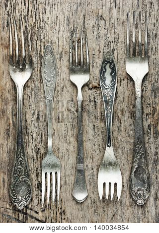 Vintage forks collection on old wooden background top view