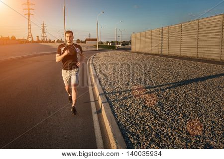 Close-up portrait of athletic man running along beautiful grey wall outdoors, muscular build young runner working out while jogging in the park. Sunset, with solar flare