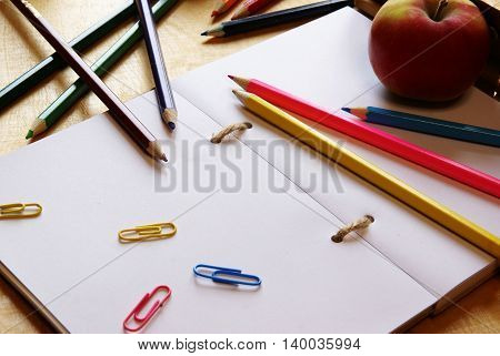 Back to school. Notepad with white sheets, color pencils, staples and fresh red apple on a wooden table. Bright colors.