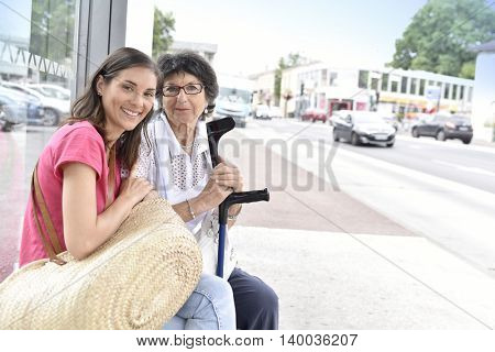 Senior woman with home carer waiting for the bus