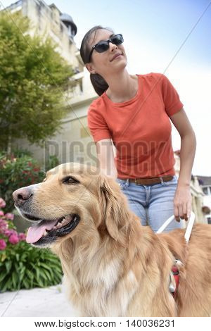 Blind woman petting her guide dog