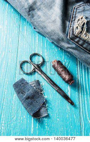 Sewing kit from pink threads, scissor and needle on jeans and wooden backround.