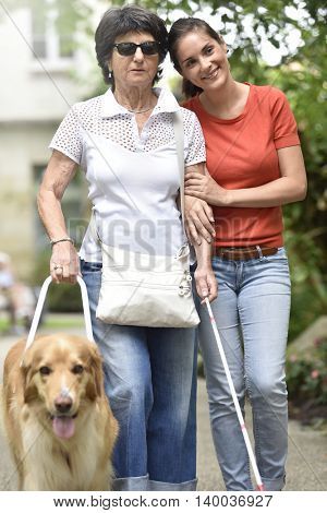 Senior blind woman walking with help of dog and carer