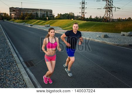 Full length portrait of athletic couple running on the road, muscular build young runners working out while jogging in the park. Evening